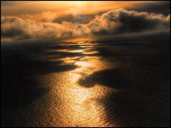 Солнце светит сквозь облака на море, оранжевый мир