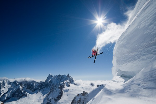 лыжник фристайлер прыгает с заснеженной горы, в ясный день