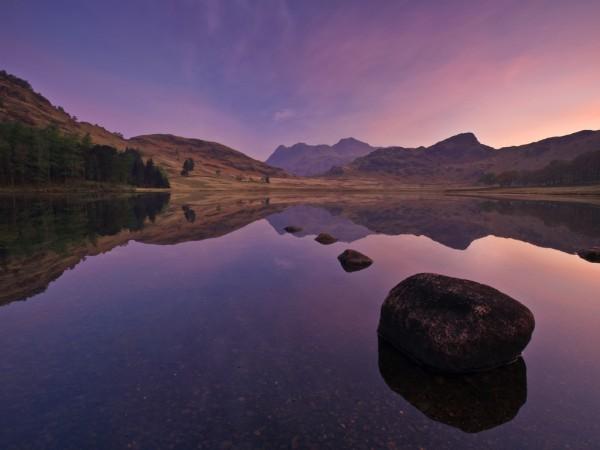 Багрово-фиолетовый закат на фоне горной глади озера, лес, камни, деревья